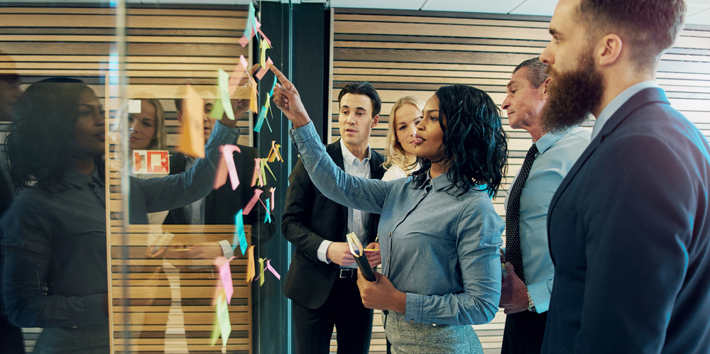 featured image Creative group of business people brainstorming putting sticky notes on glass wall in office