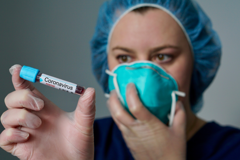 featured image Nurse wearing respirator mask holding a positive blood test result for the new rapidly spreading Coronavirus, originating in Wuhan, China
