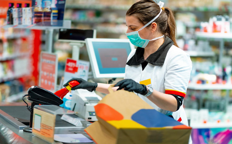 featured image of a store clerk scanning groceries while wearing a mask and gloves