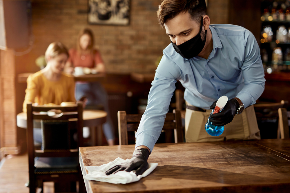 featured image showing Young waiter wearing protective face mask while cleaning tables while working in a cafe