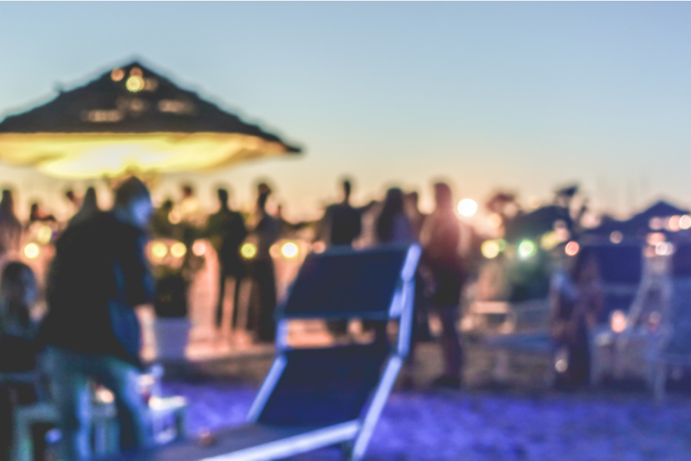 featured image blury photo of an outside beach party where people are not practicing social distancing