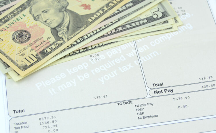 featured image Photo shows weekly salary on pay slip with US dollars in the background