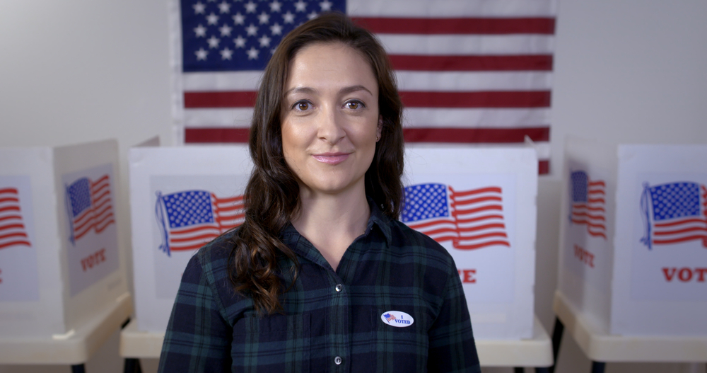 "featured image showing American woman in plaid shirt wearing ""I Voted"" sticker and looking to camera, standing proud in front of polling booths with US flag"