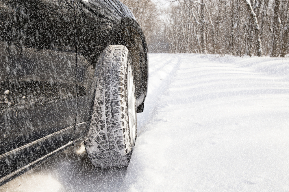 featured image showing a car driving in a snowstorm on an unplowed road