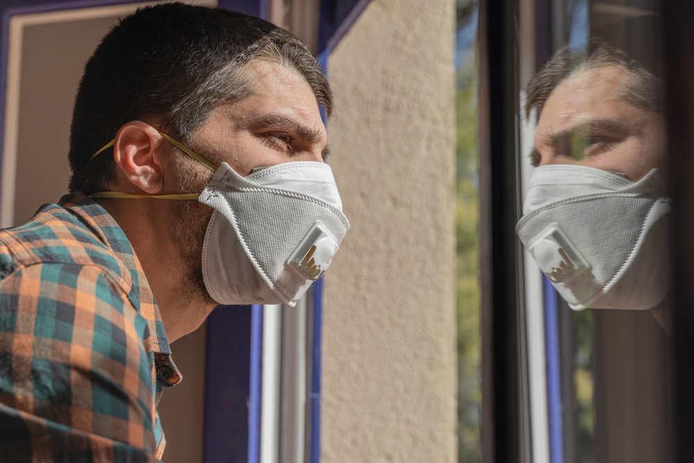 featured image showing a Sick man with Covid19 looking through the window and wearing a mask at home