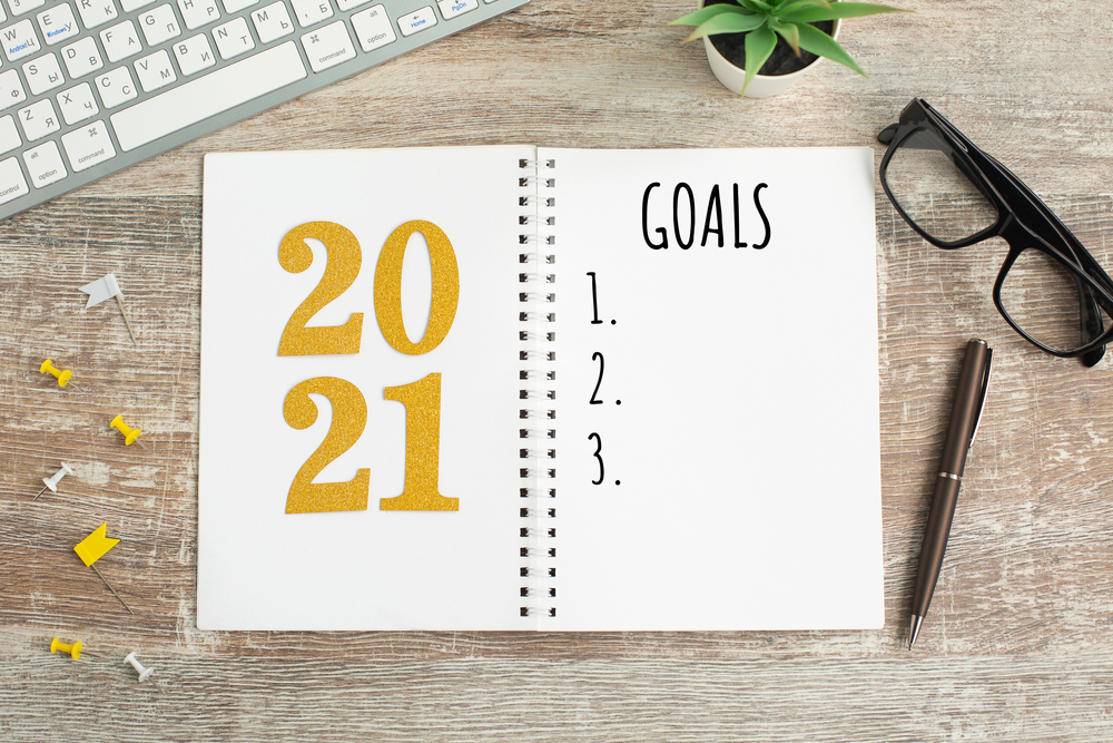 featured image showing a notebook with 2021 Goals listed on a desk by a keyboard
