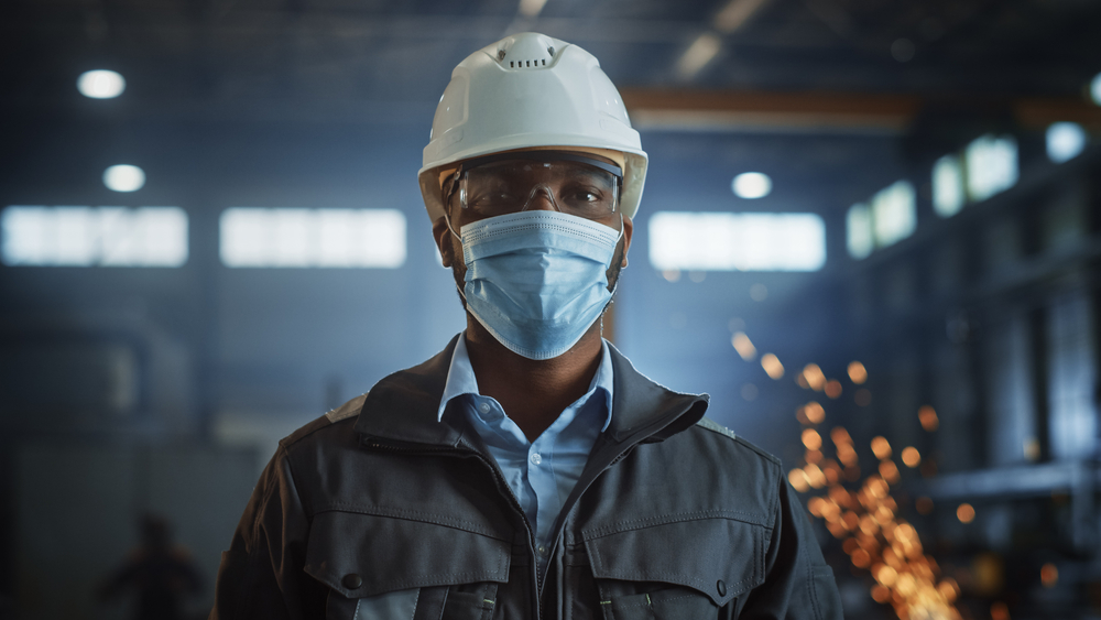 featured image showing Professional Heavy Industry Engineer Worker Wearing Safety Face Mask, Uniform, Glasses and Hard Hat in a Steel Factory