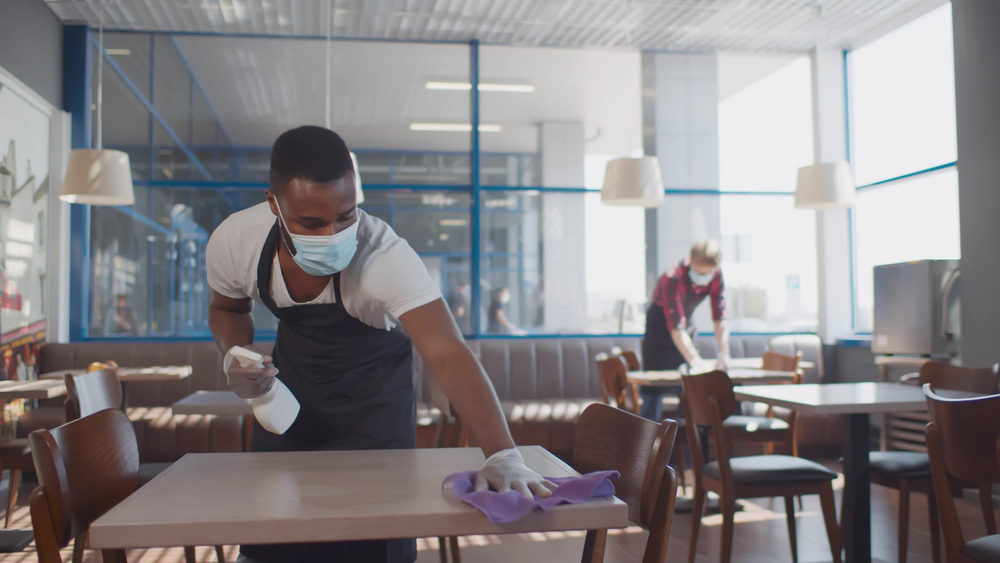 featured image showing worker cleaning table with disinfectant in restaurant during coronavirus outbreak