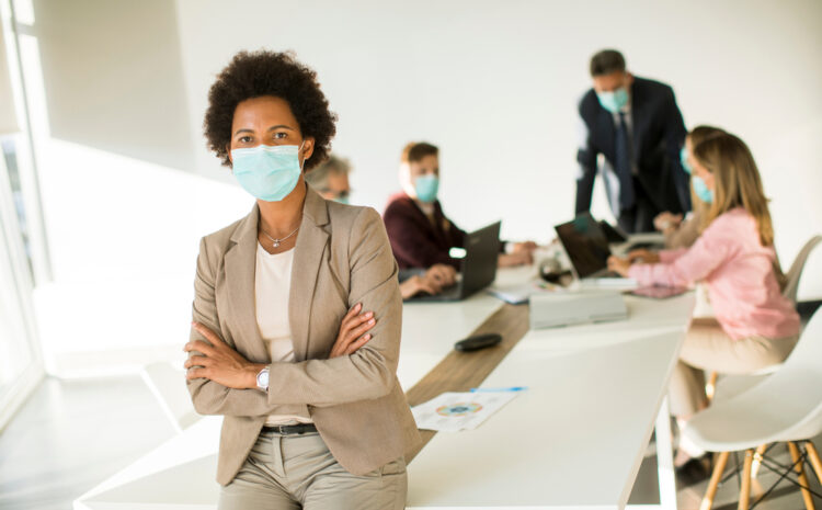 featured image showing a masked women in a conference room with three other masked employees