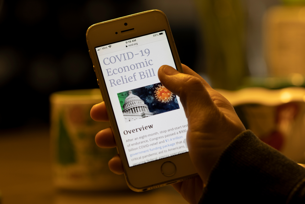 featured image showing Woman browses the National Conference of State Legislatures website to learn more about the Covid-19 Economic Relief Bill by the Biden Administration