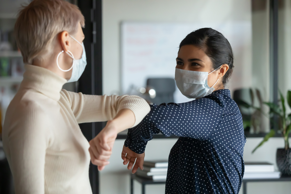 FEatured image showing diverse female colleagues wearing protective face masks greeting bumping elbows at workplace