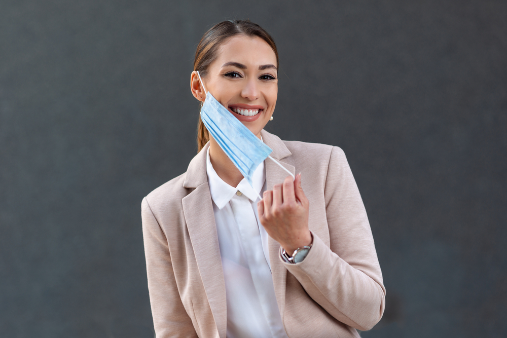 featured image showing a young business woman taking her medical mask off