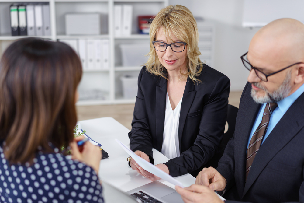 featured image showing Business partners, a middle-aged man and woman, conducting a job interview reading the female applicants CV with serious expressions