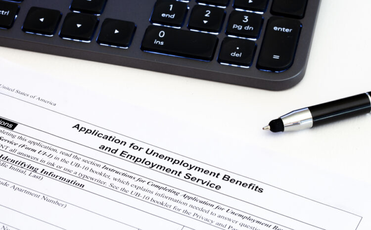 featured image showing an application for employment benefits form with computer keyboard and pen on white background